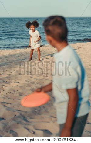 Siblings Playing With Flying Disk On Beach