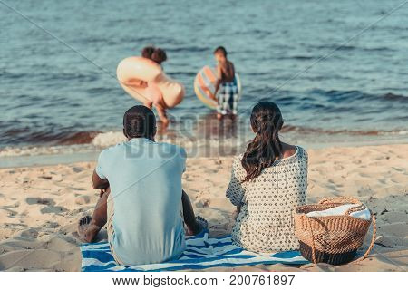 Parents Looking At Kids Playing In Sea
