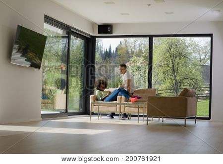 Young multiethnic couple relaxing at luxurious home with tablet computers reading in the living room on the sofa couch.
