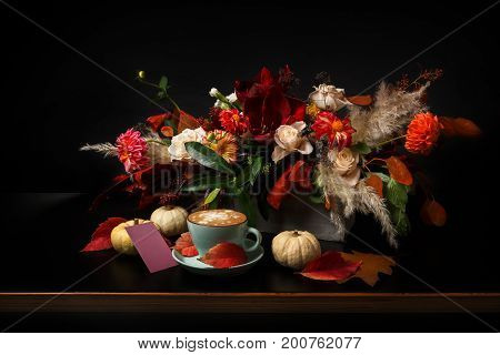 Fall flowers bouquet background on black. Colorful and warm autumn composition with cappuccino, pumpkins and empty postcard on wooden table. Holiday and floral design concept, copy space