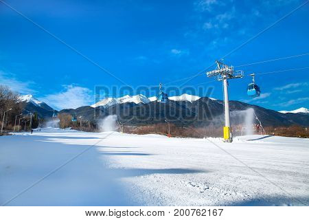 Bansko, Bulgaria - February 19, 2015: Bansko cable car cabin, ski slope and snow mountain peaks at the background