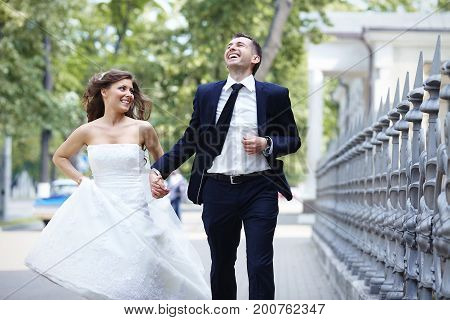 Happy bride and groom running laugh laughing on wedding day.