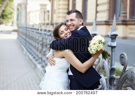 Happy bride and groom laughing smiling hugging on wedding day.