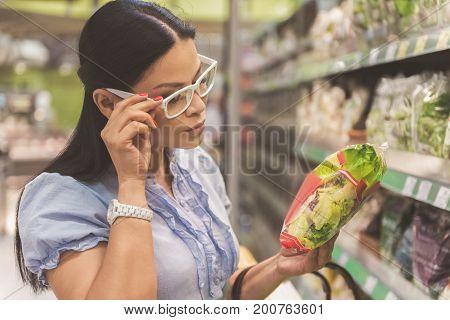 Thoughtful asian female customer looking through ingredients in modern supermarket
