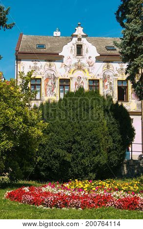 Beautiful flowering garden in the historic center of Kutna Hora with decorated old palace