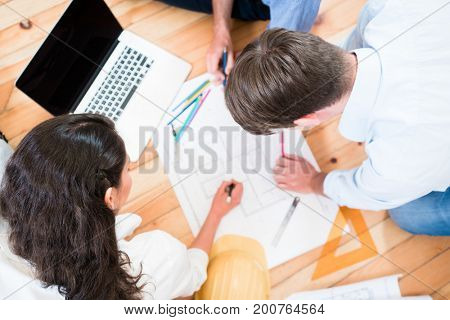Architects or civil engineers bent over construction plans on the office floor