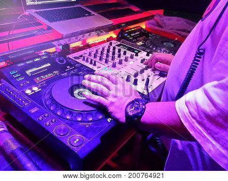 DJs are turntablism turntables plate mixer night party pub with light sunset background.
