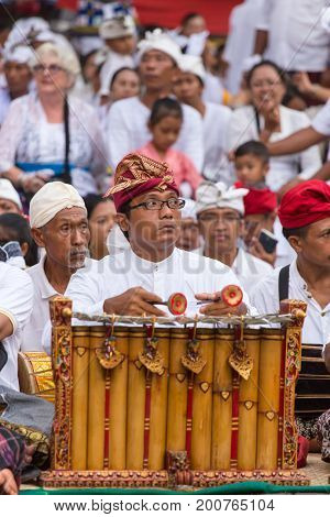 Bali, Indonesia - September 17, 2016: Unidentified balinese man playing traditional Balinese music instrument gamelan.