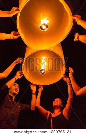 Chiang Mai, Thailand - November 14, 2016: Unidentified tourists release Khom Loi, the sky lanterns during Yi Peng or Loi Krathong festival in Chiang Mai, Thailand.
