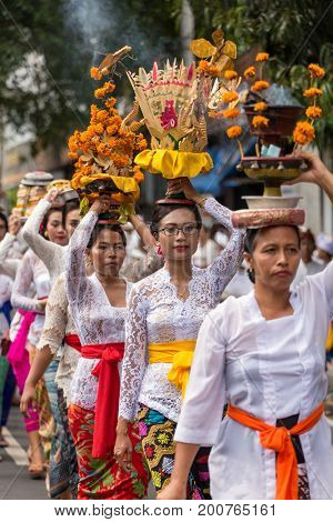 Bali, Indonesia - September 17, 2016: Procession of beautiful Balinese women in traditional costumes - sarong, carry offering on heads during Galungan celebration in Bali.
