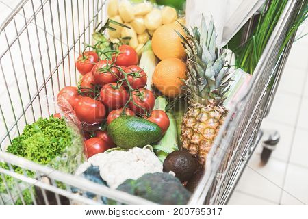 Close up basket with various fresh multicolored products situating in modern shop
