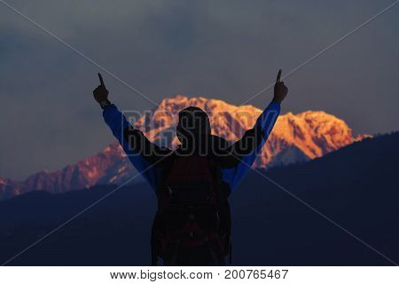 Hiker young man with backpack looking at mountain range and put hands up. Trekker man trekking in Nepal trekking route around Himalaya Mountain. Tourist traveling in holiday in the beginning of winter.