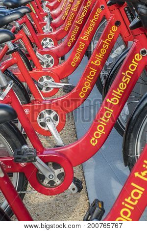 Washington DC, United States of America - August 5, 2017: Row of Red Bicycles Used in the Capital Bikeshare Program Resting on the side walk in front of the Department of Labor