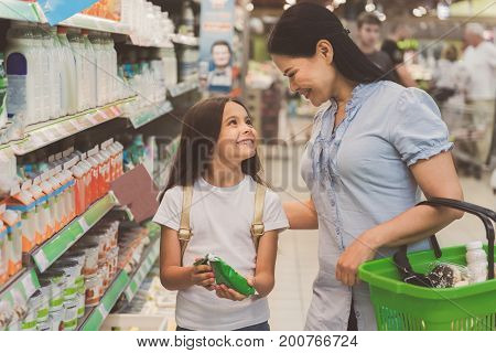 Smiling child showing milk to beaming mother in shop. Outgoing mom keeping basket with food in hand