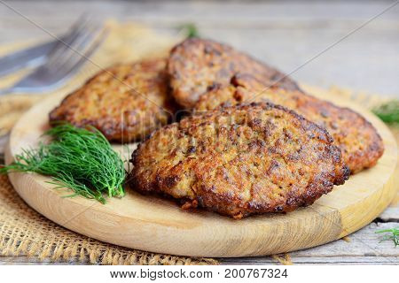 Spiced chicken liver pancakes with vegetables. Home fried chicken liver pancakes on a wooden board. Chicken liver side dish recipe. Old wooden background. Rustic style. Closeup