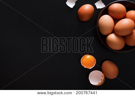 Fresh chicken brown and white home eggs with cracked eggshell and yolk on black background. Top view with copy space. Rural still life, natural healthy food and organic farming concept.