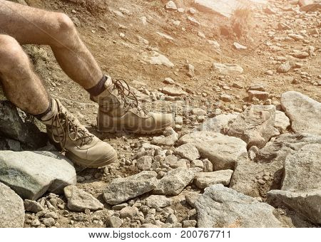 Military boots on the man's feet desert rocks