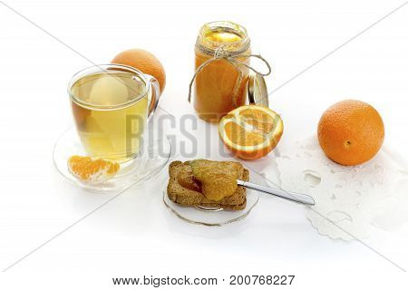 Orange jam in a jar, tea in a cup, oranges and rusks on a wooden table close-up