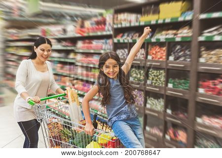 Hilarious woman is pushing product cart her daughter sitting at. Little girl glancing ahead with smile. Focus on female people and truck. Portrait