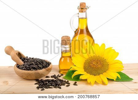 Sunflower oil, seeds and flower on wooden table with white background.