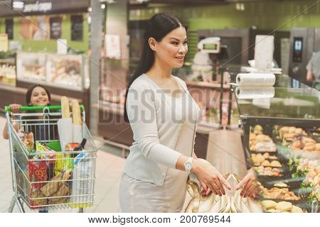 Happy mother is standing near shop-window and pointing at dishes she needs. Curious daughter locating behind product car