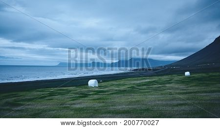 the austere Icelandic landscape with field in the foreground and the mountains and the fjords and the ocean in the background