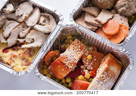 Healthy food delivery. Take away of natural fitness dishes for diet. Daily meals in foil boxes on white background, closeup