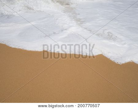 White soft sea foam wave layer with brown sand on beach in sunny day for background.