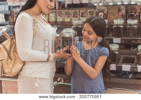 Curious little girl is looking at brown seeds in transparent jar, her smiling mother carefully holding. They standing near showcase with such goods