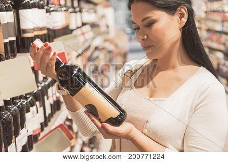 Concentrated adult lady is standing near shelves in supermarket and choosing wine. She looking at bottle, she taking with interested smile. Profile