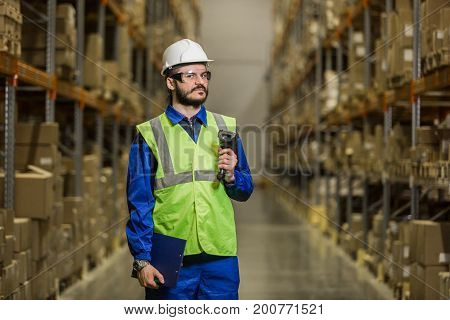 Warehouse worker in hard hat with scanner looking at camera