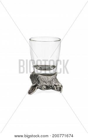 Glass for vodka with a bottom in the shape of an inverted boar head isolated on white background