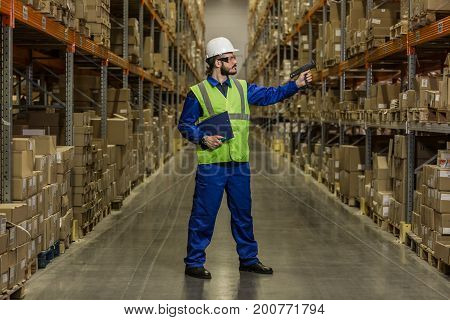 Warehouse worker checking cargo on shelves with scanner