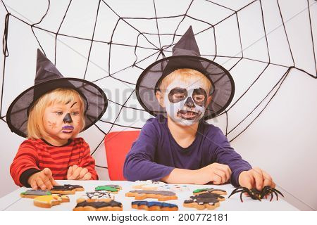 little girl and boy prepare for Halloween party