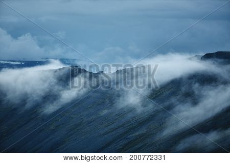 the austere Icelandic landscape with the mountains and the fjords in the background. fog under the mountain ridge