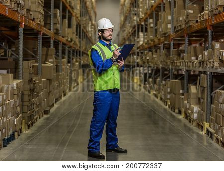 Warehouse worker in hard hat and glasses looking at checklist