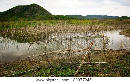 The old fish trap on the beach the lake with dry stalks poked in the water behind the beautiful green mountains. Rural atmosphere is happy.