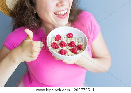 Smiling woman hold healthy and natural breakfast, oatmeal and raspberries in a bowl.