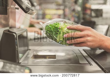 Woman is holding packed lettuce leaves above special equipment at cash machine. Close up of female hands keeping bag