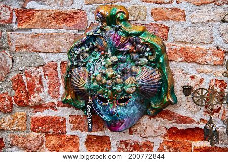 A very colorful carnival mask on a brick wall.
