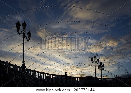 Moscow Russia. The view from the square in the blue sky with feather clouds over a curved teardrop-shaped jet of water from the town fountain. Are the street lights.