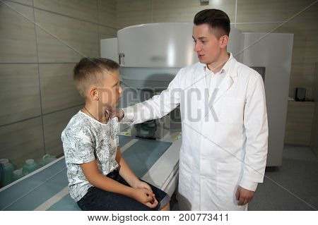 VINNITSA, UKRAINE, JULY 27, 2017: CT scanner with patient and doctor. Patient being scanned and diagnosed on a computed tomography. Doctors examine the child on a tomograph.