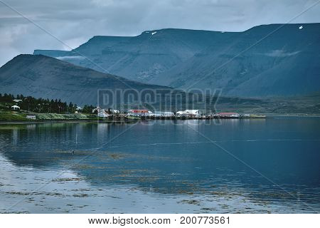 Travel to Iceland. beautiful sunset over the ocean and fjord in Iceland. Icelandic landscape with mountains, sky and clouds. View of Flateyri, a village in the north-west of Iceland, on the Westfirdir peninsula