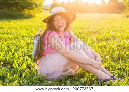Beautiful young laughing naughty woman sitting outdoors and smiling.