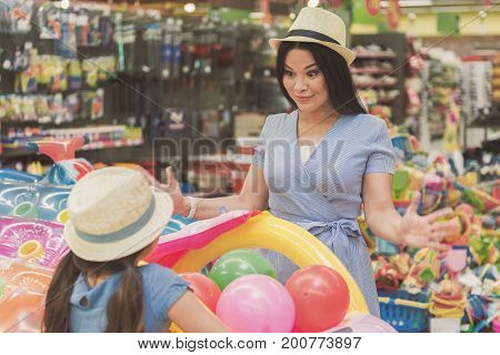 Surprised mother is looking at daughter with sincere smile. They standing near inflatable toys and deciding what to buy. Copy space on left side. Waist up portrait