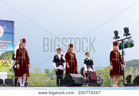 ADYGEA RUSSIA - AUGUST 19 2017: Children's dance group in traditional Circassian clothes at the open Adyghe cheese festival