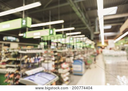 Various goods are on shelves near cashboxes. Defocused picture of supermarket aisle. Copy space