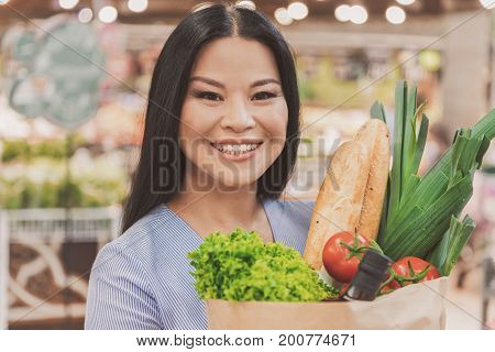 Cheerful female consumer is standing in supermarket and holding package full of food. She glancing at camera with sincere smile. Portrait. Copy space on left side