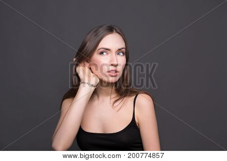 Young woman trying to listen gossip. Very curious girl holding her hand near ear, trying to hear something