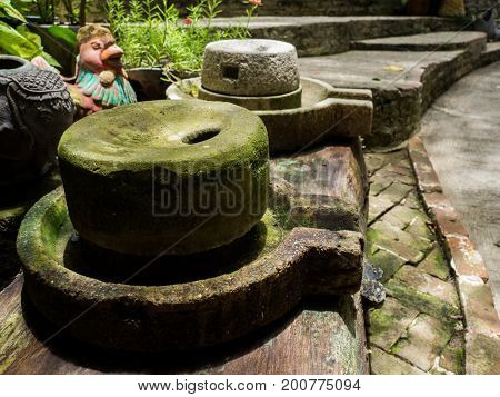 Ancient millstone have green lichen around and Ancient millstone put on old wooden boards